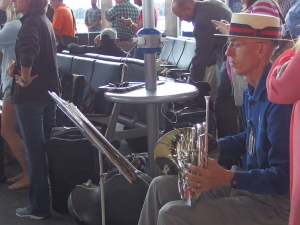To the right of the photo, an older man in a straw hat with a red and blue hat band sits holding a French horn, looking toward a music stand with sheet music.  In the background, an airline terminal with passengers standing facing the same direction as the musician, some clapping.