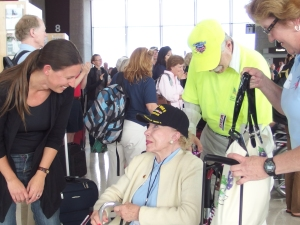 An older woman in a wheelchair in an airport terminal.  She wears a ballcap that says World War II veteran.  She is beautiful and is wearing elegant make up, nail polish and jewelry, as well as a blue polo shirt and white sweater.  To the left of the photo, a younger woman leans in, smiling, to speak to the woman in the wheelchair, while a man in a bright yellow shirt and hat stands behind the wheelchair.  In the back ground, a crowd of people look toward an airport gate, clapping.