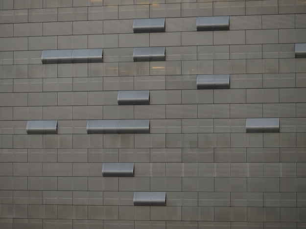 Photo of the side of a building with brick shaped windows, some of which are open and jutting out.