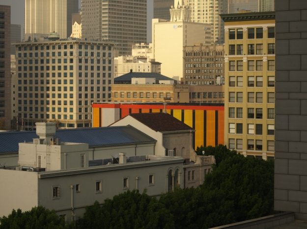 Photo of buildings. Most are beige. One low building in the center is bright red and yellow.