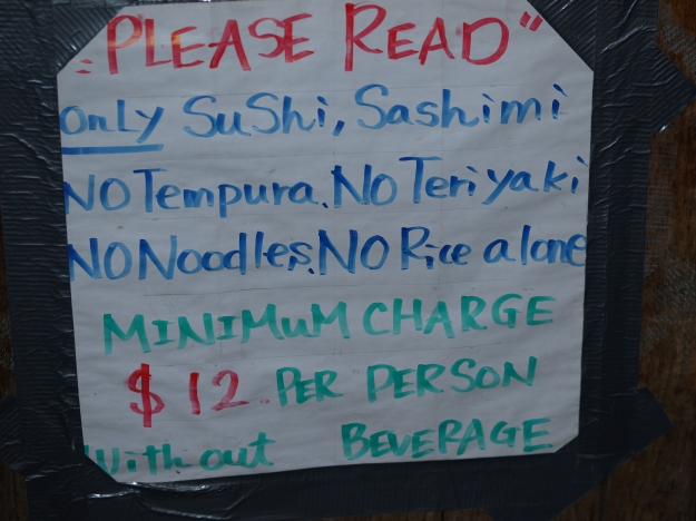 """Photo of hand-lettered sign that reads """"please read. only sushi, sashimi. no tempura. no teriyaki. no noodles. no rice alone. minimum charge $12 per sperson without beverage."""""""
