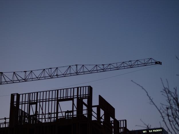 Photo of construction crane and building framework at dusk.