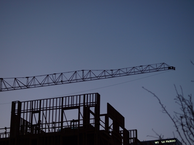 Photo of construction crane and building framework at dusk.