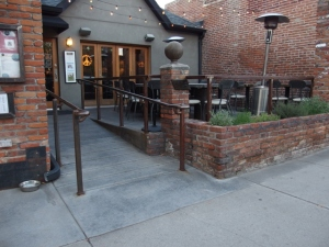 Photo showing front of restaurant with a ramp to the front entrance adjacent to a patio area with tables and seats.