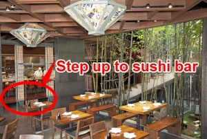 "Photo of the inside of a restauarant.  To the lower left of the photo, a raised area is visible with seats at a lowered sushi bar.  The raised area is circled in red, with an arrow pointing to it from text that reads ""Step up to sushi bar."""