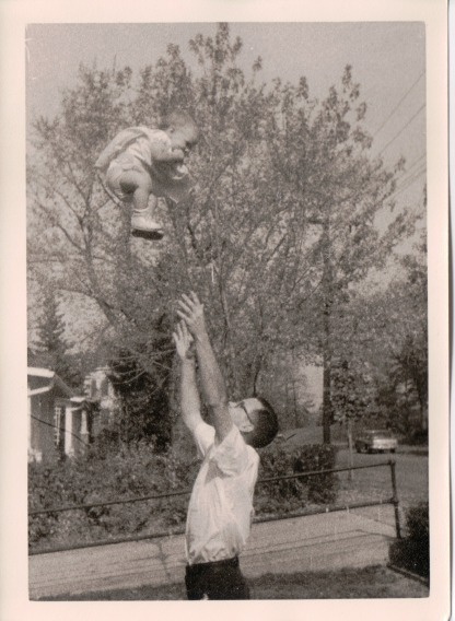Image:  Black and white photo from about 1962 of man in his 20s  in a white shirt and dark pants who has tossed a toddler into the air about two feet over his head.  His hands reach up to her, while her hands are at her mouth giggling.