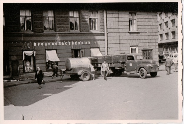 {Black and white photo of an old time pick up truck towing a small tank of liquid, parked in front of a building.}