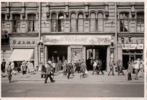 {Black and white photograph of people walking in front of a building with a large banner in Russian.}