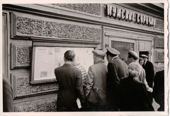 {Black and white photo of men gathered in front of a newspaper that is posted on the exterior wall of a building.}