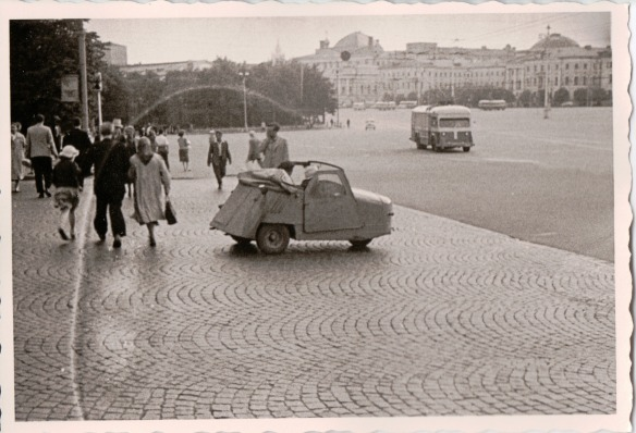 {Black and white photo of a cobblestone street and sidewalk.  In the foreground is a very small three-wheeled vehicle, suitable for at most one person, open on top and looking almost home-made out of pieces of welded steel.  In the background are pedestrians and in the far background, indistinct buildings.}