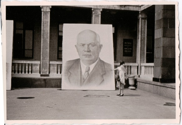 {Black and white photo of a building with a giant portrait of Nikita Khruschev leaning against the columns in the front of the building.  The portrait is over twice the height of a man standing near it.}