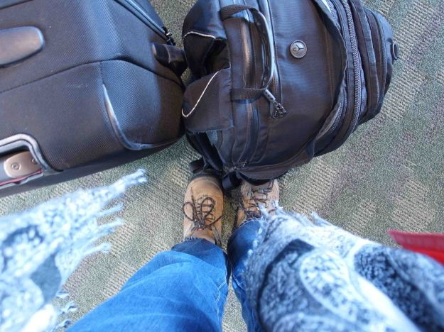 {Image: photo of the photgrapher's feet taken looking straight down.  Feet are in hiking shoes; jeans and the end of a scarf are also visible, as are two pieces of luggage.}