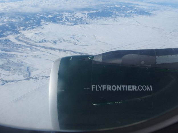 "{Image: photo taken from the window of a plane. In the right foreground is the engine with the legend ""FlyFrontier.com.""  In the background, snow covered foothills.}"
