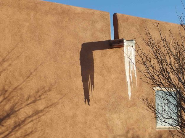 {Image:  a flat water spout protrudes from an adobe wall with several feet of frozen water suspended off the end.}