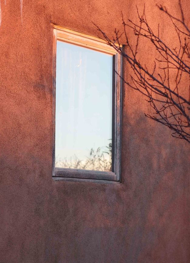 {Image:  a window in an adobe wall.  The window reflects a very blue sky.  Tree branches enter the photo from the right.}