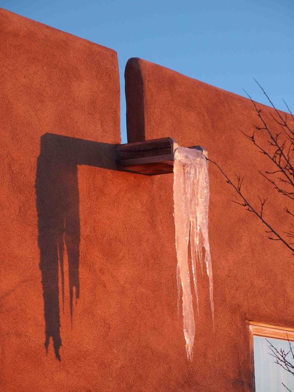 {Image:  a flat water spout protrudes from an adobe wall with several feet of frozen water suspended off the end.  The adobe is much darker than the previous photo because of the setting sun.}}