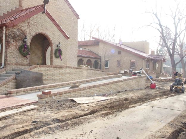 {Image:  photo of a church buliding with -- in front of the church -- a long concrete and brick ramp under construction.}