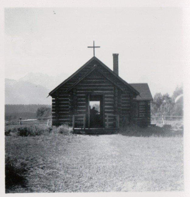 {Image:  Black & white photo of a small log church with a cross on top.}
