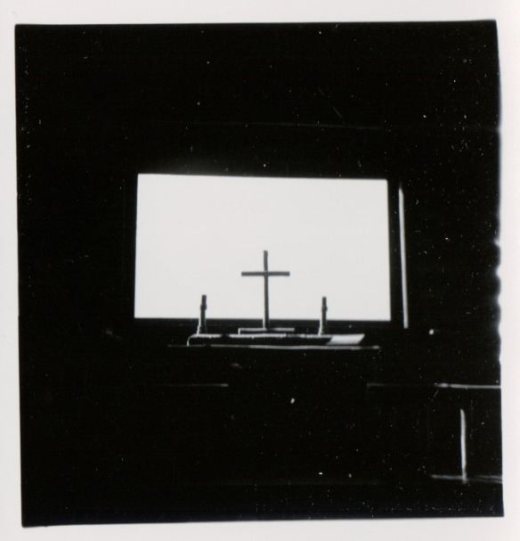 {Image:  black and white photo of a rectangular window with a cross silhouetted against the middle.}