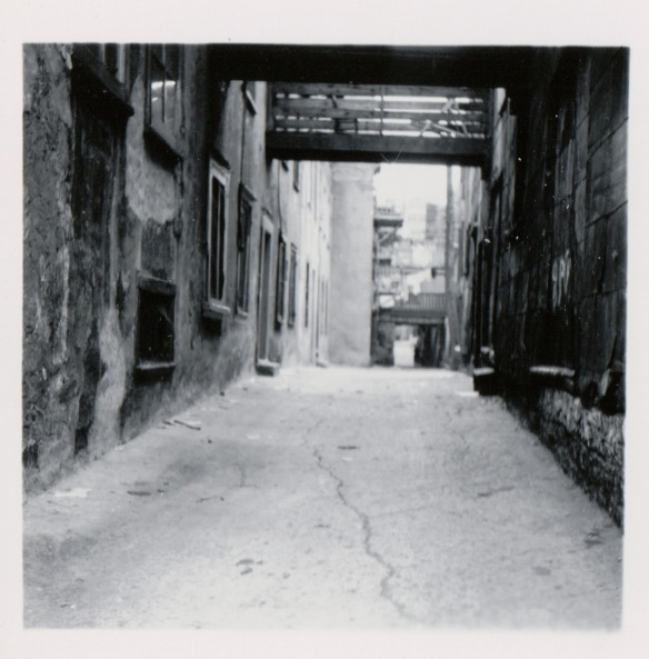 {Image: black & white photo of a narrow alley with brick buildings on either side and passageways overhead.}