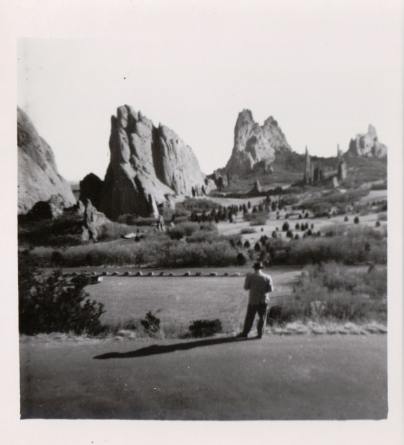 {Image:  black & white photo of Garden of the Gods, which is a series of rock formations in a high-desert landscape.  A man is in the foreground looking at the scenery.}