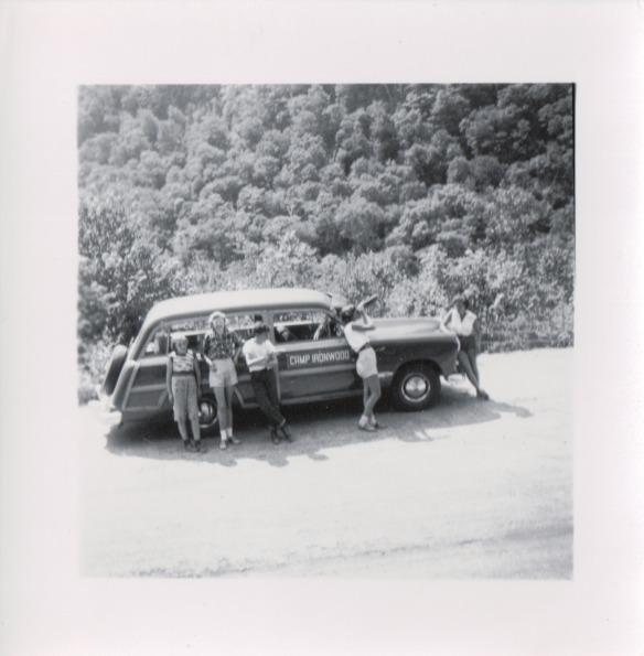 {Image:  1940s wood-paneled station wagon parked at the side of the road.  Five teen agers lean against it, one of whom is looking through a lens of some sort; the others facing the camera.}