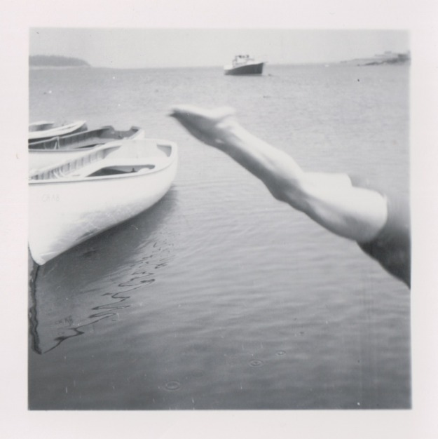 {Image: black and white photo of a person diving into the water, but all we see is the person's legs, perfectly straight, angled from their toes at the center of the photo to the bottom right where their torso disappears off the edge of the photo. To the left are several canoes, and in the background, a boat.}