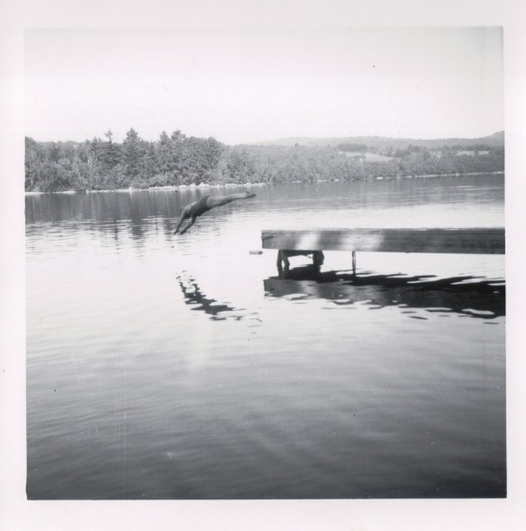 {Image: black and white photo of a person diving off of a dock into a lake.  The diver's image is reflected in the lake.}