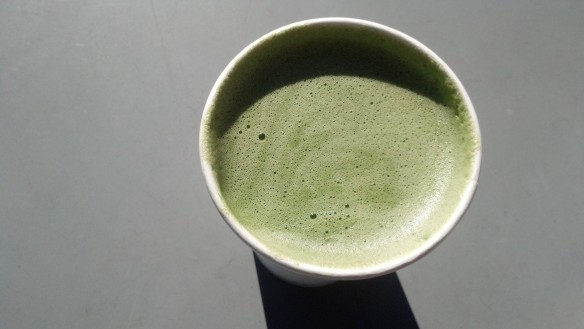 {Image:  overhead view of cup filled with slightly foamy green liquid.}