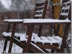 {Image:  two wooden slatted patio chairs with about a half-inch of snow.}