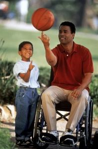 {Image: Photo of boy and man. Both are African-American. The man is on the right, sitting in a manual wheelchair, spinning a basketball on his finger. The boy stands to his side, watching the basketball and holding up one finger as if to imitate the man.}