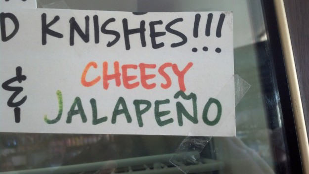 """{Image:  photo of handwritten sign advertising """"Knishes!!! Cheesy Jalapeno.""""}"""