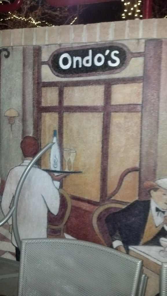 "{Image:  painted mural with a waiter carrying a tray with a bottle, viewed from the back, and a store front with the logo ""Ondo's""}"