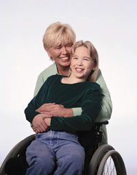 {Image: a woman and girl, both white, both blond. The girl is in a manual wheelchair. The woman hugs her from behind.}