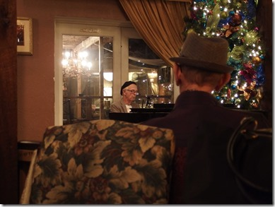 {Image:  photo.  in the left foreground, the back of a brocade (flowered) chair.  right foreground: the back of the head of an older gentleman with a short haircut and a hat.  To the right in the background, a Christmas tree with lights.  In the center, an older man in a beret playing the piano.}