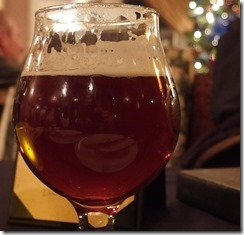 {Image:  close up of a glass of dark beer.  christmas tree with lights in the right background.}