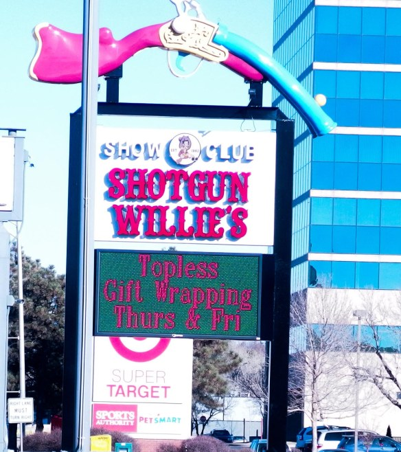 "{Image:  signage from front of the Denver strip club called ""Shotgun Willie's.""  The sign reads, ""Topless Gift Wrapping Thurs & Fri.""  The Shotgun Willie's logo above the sign is an oversized shotgun, arcing downward.}"