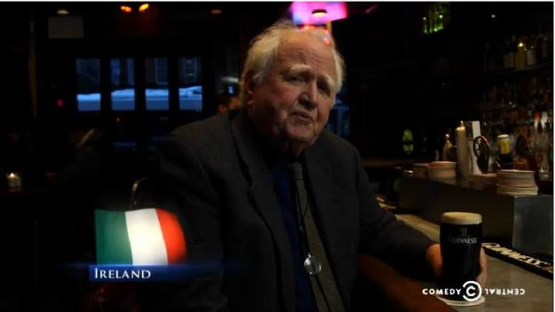 "{Image: an older white man sits at a bar with a full glass of dark beer in a Guinness glass; image of the Italian flag (three horizontal green, white and orange stripes) and the word ""Ireland"" in the lower lefthand corner.}"