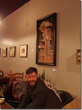 {Image:  photo of a white man with short brown hair and a beard sitting in an upholstered chair looking toward the camera.  Above and to his right is a painting perhaps 3 feet high by 2 feet wide of a person standing facing the viewer with his hands held out in front of him as if to show something.  In the background of this large painting are buildings.  In the background of the photo are additional, smaller paintings and other chairs and tables in a coffee shop.}
