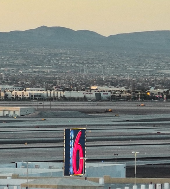 "{Image:  sunrise over the mountains, but in the foreground, a busy airport runway and the neon ""6"" of a Motel 6 sign.}"