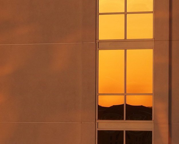 {Image:  mountains and sunrise reflected in the windows of a highrise building.}