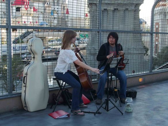 {A female cellist with cello and a male violinist with violin on a pedestrian bridge over a street in Las Vegas; the background full of neon signs and traffic.}