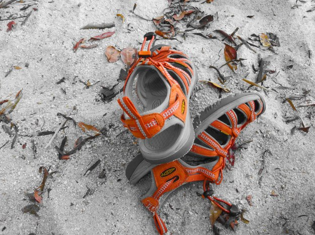 Image: orange sandals in the sand.
