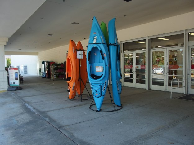 {Image:  orange and blue plastic kayaks displayed in front of a Kmart store.}