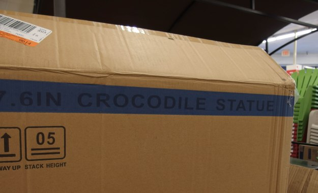 "{Image: : Cardboard packing box with the words ""crocodile statue"" on the outside.}"