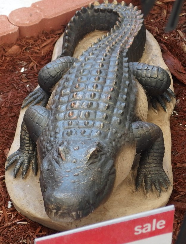 {Image:  A garden-sized statue of a crocodile.}