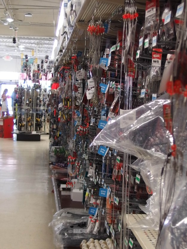 {Image:  on the right side of the photo, the display racks on one side of an aisle of a Kmart store, all showing fishing gear of various types.  The left side of the photo showing a clear path down the aisle.}