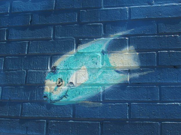 {Image:  close up of part of the mural showing a single teal-colored fish.}