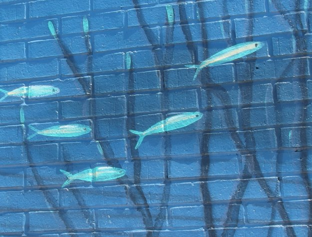{Image:  close up of part of the mural showing a five small teal-colored fish.}