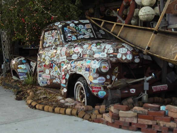 Image:   Old pick-up truck body, embedded in a brick sidewalk, covered with stickers.